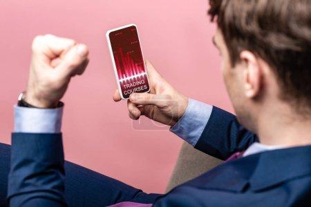 Photo pour Vue recadrée de l'homme d'affaires réussi utilisant le smartphone avec l'application de cours de négociation, d'isolement sur le rose - image libre de droit
