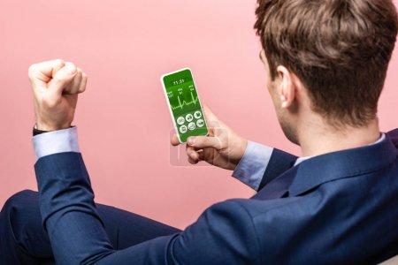 Photo pour Vue recadrée de l'homme d'affaires réussi utilisant le smartphone avec l'application de santé, d'isolement sur le rose - image libre de droit