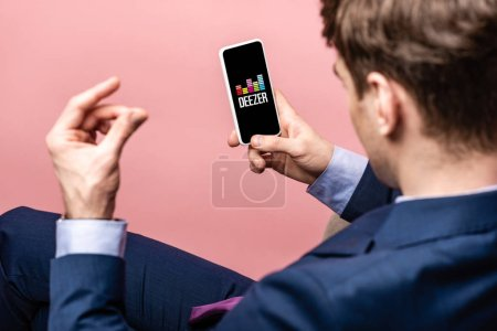 Photo for KYIV, UKRAINE - MAY 16, 2019: cropped view of businessman using smartphone with deezer app, isolated on pink - Royalty Free Image