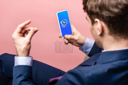 Photo for KYIV, UKRAINE - MAY 16, 2019: cropped view of businessman using smartphone with shazam app, isolated on pink - Royalty Free Image