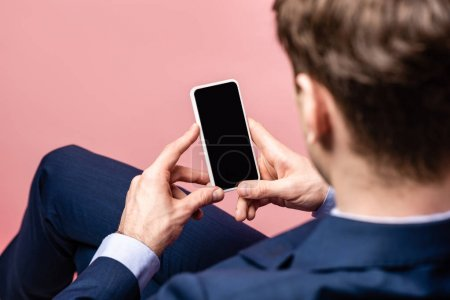Photo for Back view of businessman sitting and holding smartphone with blank screen isolated on pink - Royalty Free Image