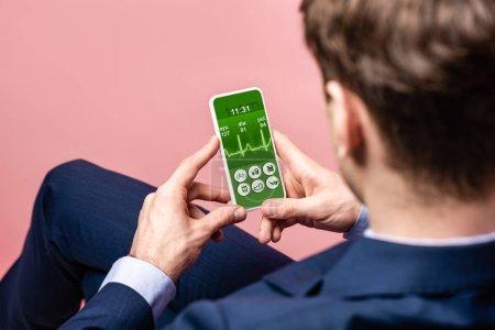 Photo pour Vue recadrée de l'homme d'affaires utilisant le smartphone avec l'application de santé, d'isolement sur le rose - image libre de droit