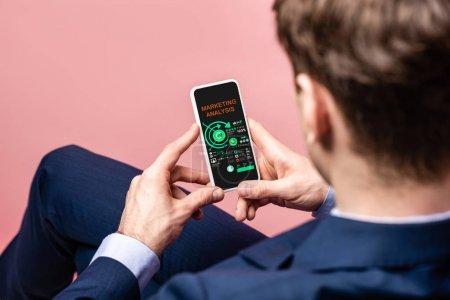 Photo pour Vue recadrée de l'homme d'affaires utilisant le smartphone avec l'analyse de marketing, d'isolement sur le rose - image libre de droit