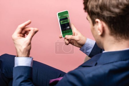 Photo for Cropped view of businessman using smartphone with booking app, isolated on pink - Royalty Free Image
