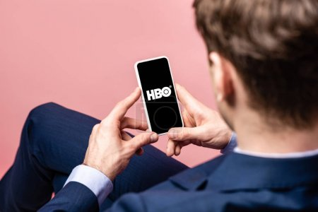 Photo for KYIV, UKRAINE - MAY 16, 2019: cropped view of businessman using smartphone with HBO app, isolated on pink - Royalty Free Image