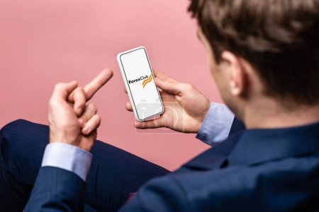 Photo for KYIV, UKRAINE - MAY 16, 2019: cropped view of businessman using smartphone with forex club app and showing middle finger, isolated on pink - Royalty Free Image