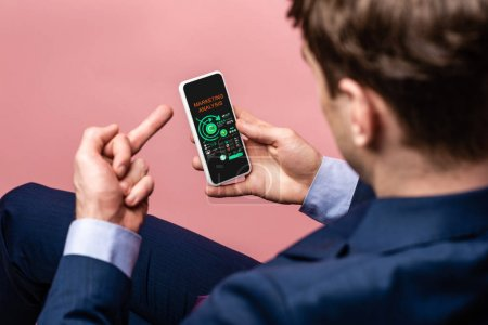 Photo for Cropped view of businessman using smartphone with marketing analysis app while showing middle finger, isolated on pink - Royalty Free Image