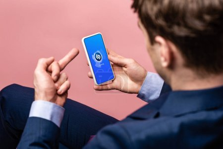 Photo for KYIV, UKRAINE - MAY 16, 2019: cropped view of businessman using smartphone with shazam app and showing middle finger, isolated on pink - Royalty Free Image
