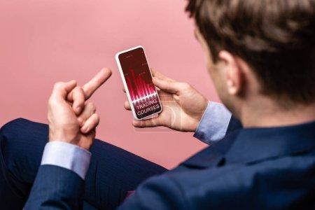 Photo pour Vue recadrée de l'homme d'affaires utilisant le smartphone avec l'application de cours de négociation tout en affichant le doigt moyen, isolé sur le rose - image libre de droit