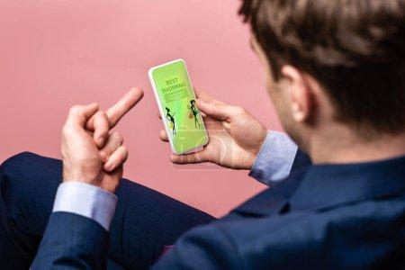 Photo pour Vue recadrée de l'homme d'affaires utilisant le smartphone avec la meilleure application d'achats tout en affichant le doigt moyen, isolé sur le rose - image libre de droit