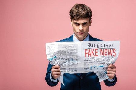 Photo pour Sérieux homme d'affaires tenant journal avec de fausses nouvelles et regardant la caméra sur fond rose - image libre de droit