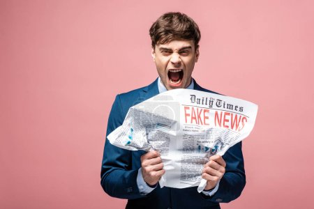 Photo for Aggressive businessman crumpling newspaper with fake news while looking at camera - Royalty Free Image