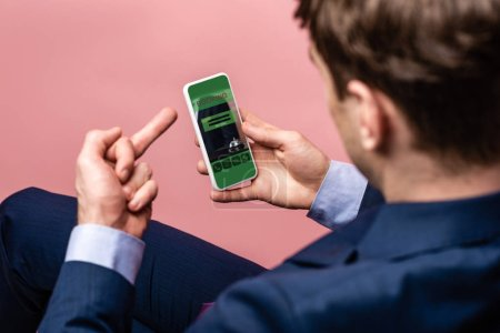 Photo for Cropped view of businessman using smartphone with booking app while showing middle finger, isolated on pink - Royalty Free Image