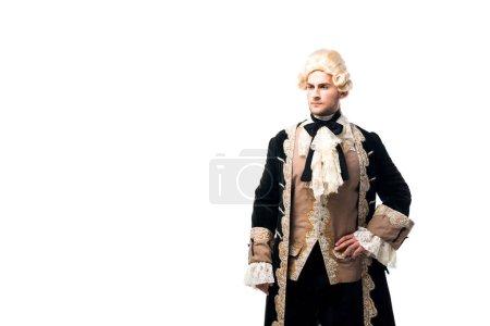 Photo pour Bel homme victorien en perruque debout avec la main sur la hanche isolé sur blanc - image libre de droit