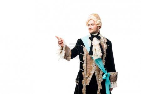 Photo pour Homme victorien heureux dans la perruque restant et pointant avec le doigt d'isolement sur le blanc - image libre de droit