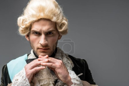 Photo for Serious victorian gentleman in wig looking at camera isolated on grey - Royalty Free Image