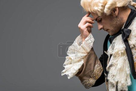 Photo pour Vue latérale du monsieur victorien pensif dans la pensée de perruque d'isolement sur le gris - image libre de droit