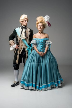 Photo for Attractive victorian woman in blue dress near handsome man with hand on hip on grey - Royalty Free Image