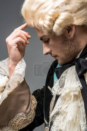 Photo for Side view of pensive victorian man in wig thinking isolated on grey - Royalty Free Image