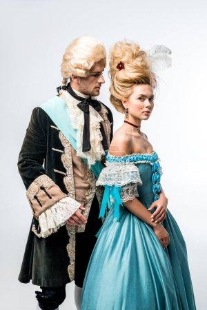 Photo pour Bel homme en perruque regardant belle femme victorienne en robe bleue sur blanc - image libre de droit