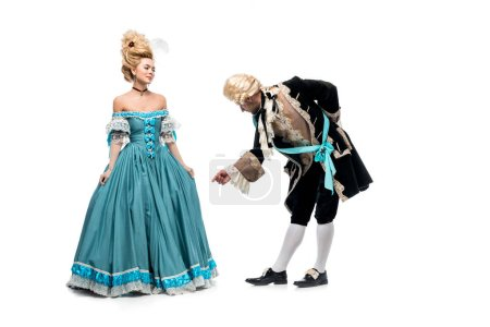 Photo for Handsome gentleman bowing down near victorian woman in blue dress isolated on white - Royalty Free Image