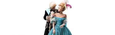 Foto de Foto panorámica de hombre victoriano pomposo mirando a la mujer atractiva en peluca aislada en blanco - Imagen libre de derechos