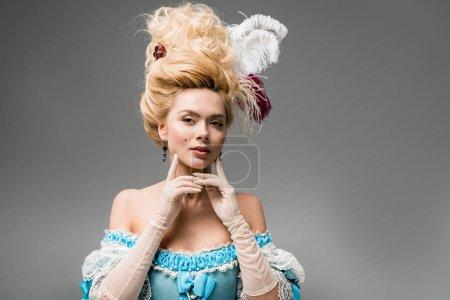 Photo pour Belle femme victorienne en perruque avec des plumes regardant la caméra et toucher le visage sur gris - image libre de droit