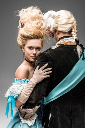 Photo for Back view of man hugging attractive victorian woman in wig on grey - Royalty Free Image