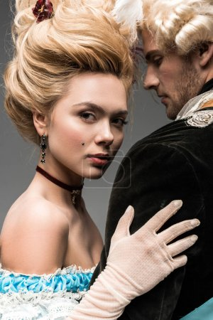 Photo for Attractive victorian woman in wig hugging handsome man isolated on grey - Royalty Free Image