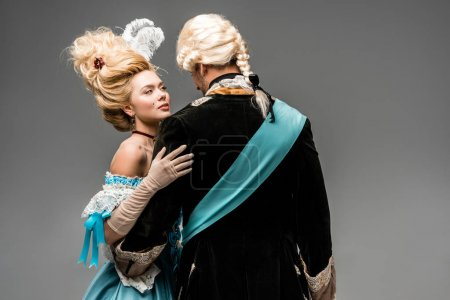 Photo for Attractive victorian woman in blue dress hugging man in wig on grey - Royalty Free Image