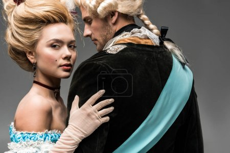 Photo for Beautiful victorian woman in blue dress hugging man in wig on grey - Royalty Free Image
