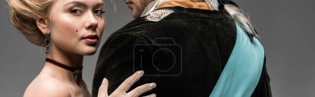 Photo for Panoramic shot of beautiful victorian woman hugging gentleman in wig isolated on grey - Royalty Free Image