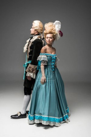 Photo for Beautiful victorian woman standing with gentleman in wig on grey - Royalty Free Image