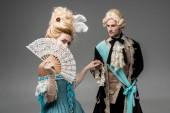 "Постер, картина, фотообои ""beautiful victorian woman covering face with fan while holding hands with gentleman on grey"""