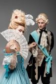 """Постер, картина, фотообои """"селективный фокус викторианской женщины, покрывающей лицо с вентилятором, держась за руки с джентльменом на сером"""""""