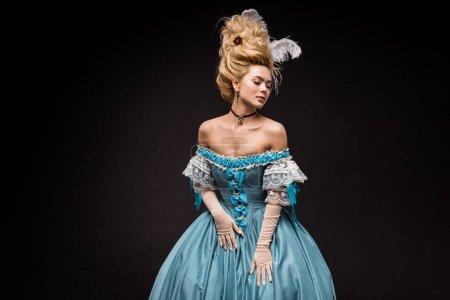 Photo pour Femme victorienne attirante dans la perruque restant et touchant la robe bleue sur le noir - image libre de droit