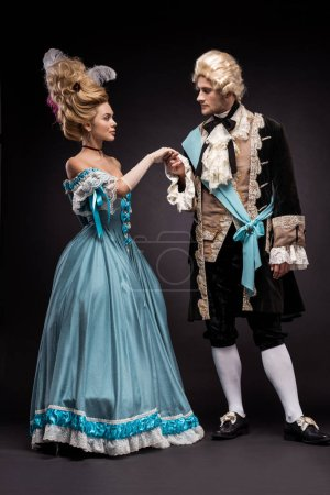 Photo for Handsome victorian man and woman in wigs standing and holding hands on black - Royalty Free Image