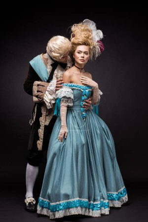 handsome victorian man looking at woman in wig while standing on black