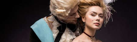Photo for Panoramic shot of handsome victorian man looking at woman in wig on black - Royalty Free Image