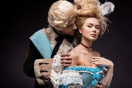 Photo for Handsome victorian man looking at young woman in wig on black - Royalty Free Image
