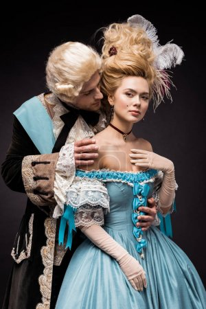 Photo for Handsome victorian man looking at young beautiful woman in wig on black - Royalty Free Image
