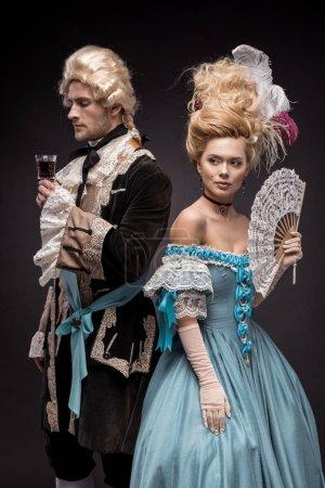 Photo pour Bel homme avec verre de vin près de femme victorienne en perruque tenant ventilateur sur noir - image libre de droit