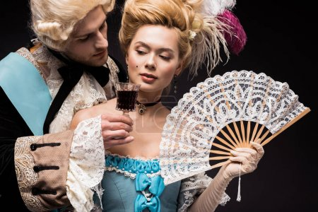 Photo for Handsome man looking at young victorian woman in wig holding fan  and wine glass isolated on black - Royalty Free Image