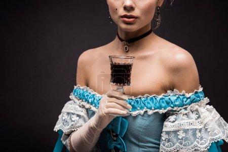 Photo pour Vue recadrée de femme victorienne retenant le verre de vin sur le noir - image libre de droit