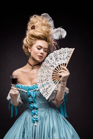 Photo for Attractive victorian woman holding fan and wine glass while standing on black - Royalty Free Image