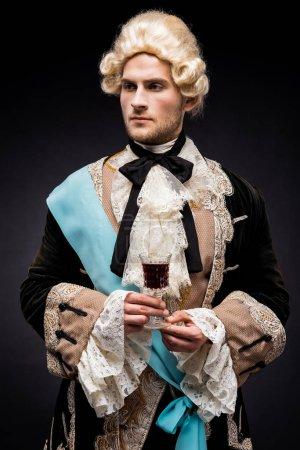 Photo pour Bel homme victorien dans la perruque retenant le verre de vin sur le noir - image libre de droit