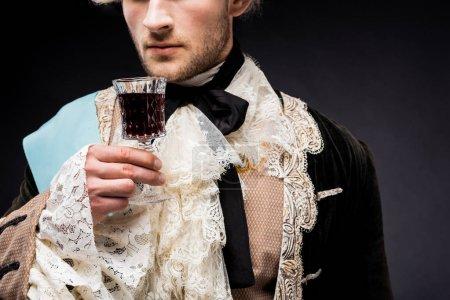 Photo pour Vue recadrée de l'homme victorien tenant verre de vin sur noir - image libre de droit