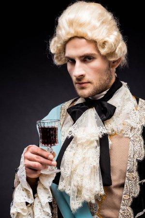 Photo pour Pompeux victorien homme en perruque tenant verre de vin sur noir - image libre de droit