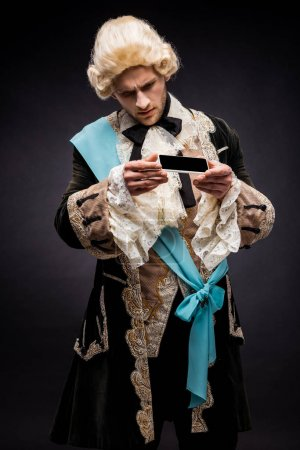 Photo for Handsome victorian man in wig looking at smartphone with blank screen on black - Royalty Free Image