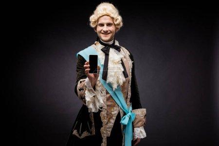 Photo pour Homme victorien beau dans le smartphone de fixation de perruque avec l'écran blanc sur le noir - image libre de droit